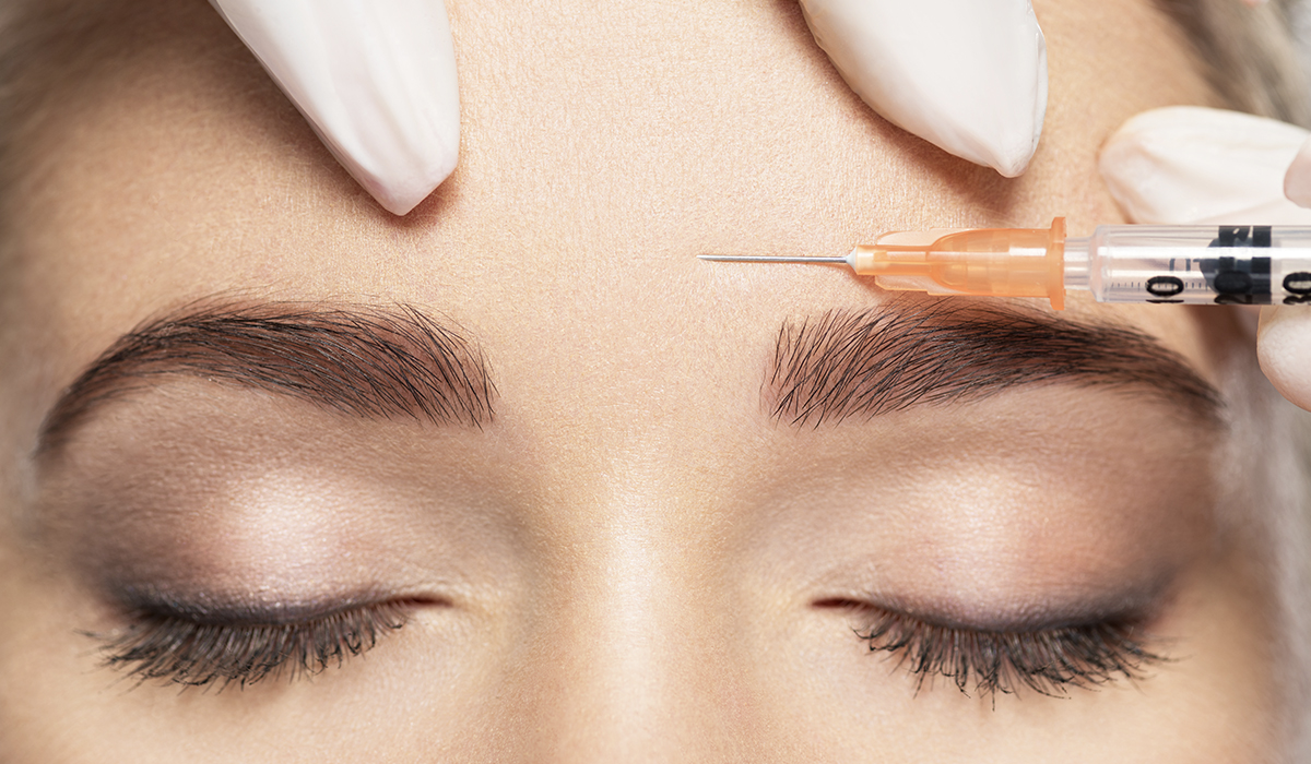 Close-up Young Beautiful Woman receiving botox on forehead