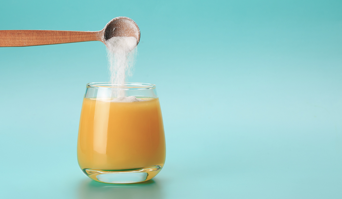 Collagen scooper pouring into juice
