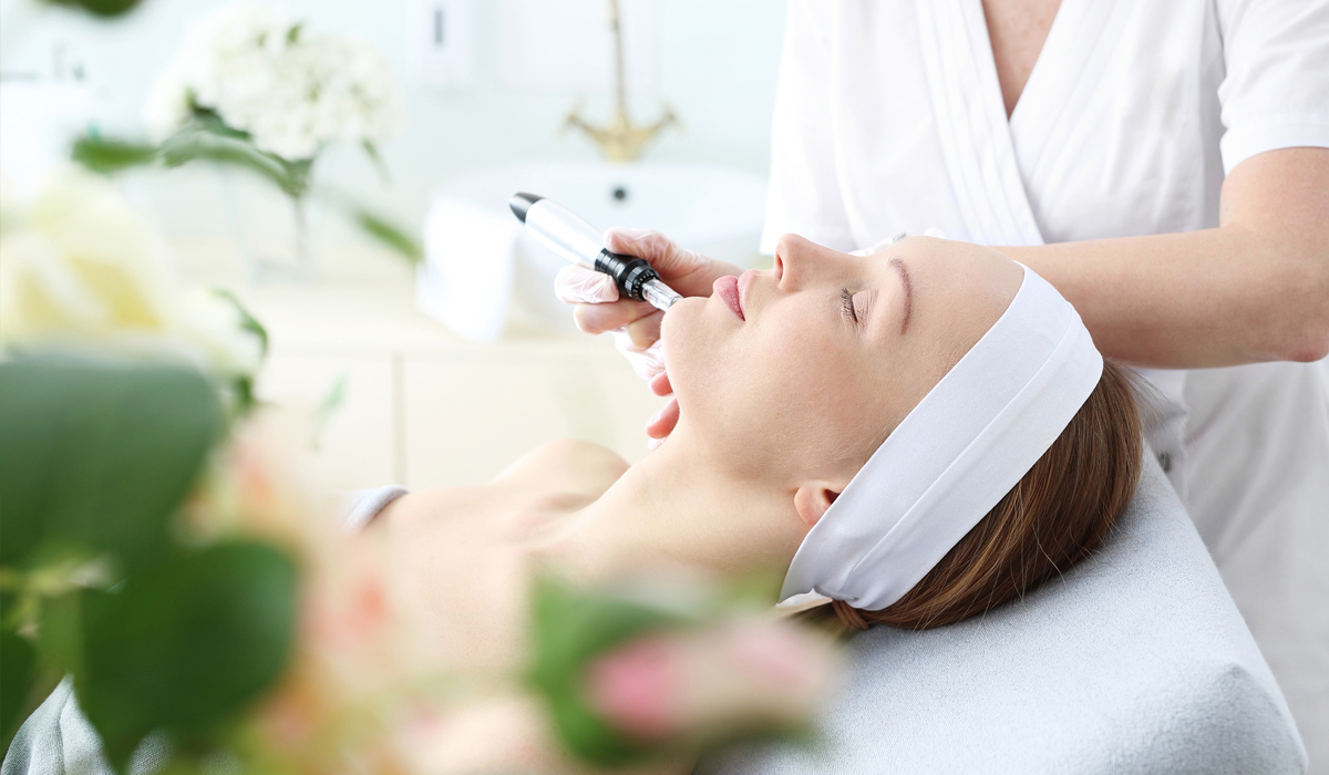 Esthetician working on patient with hydrafacial