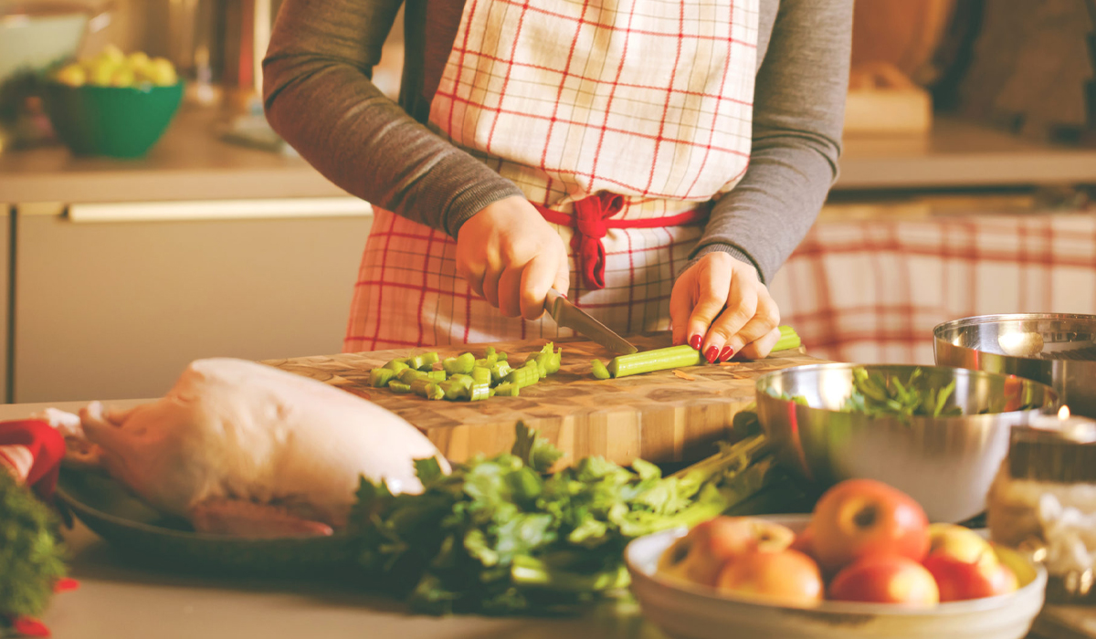 Holiday image of mother cooking and cutting celery on cutting board