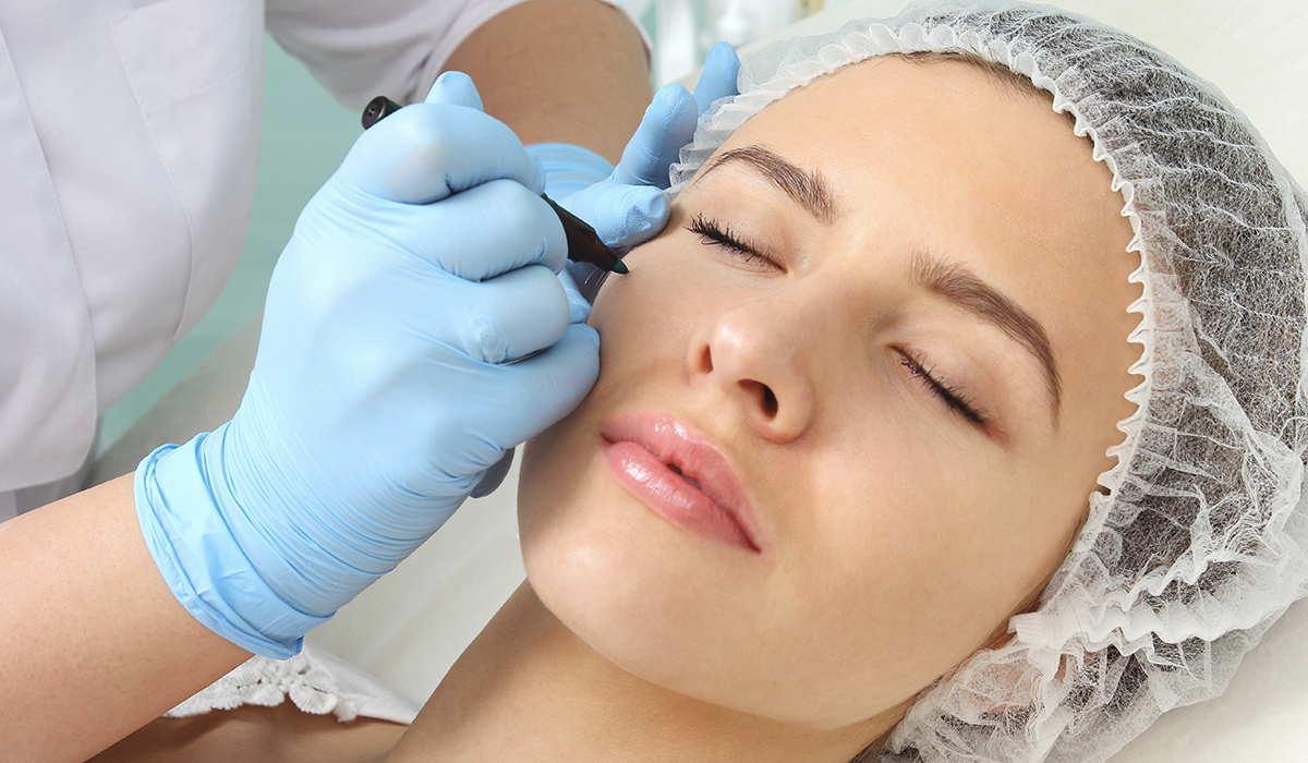 Woman patient receiving preparation for cosmetic procedure