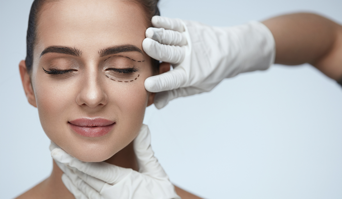 Woman with plastic surgeon drawing on face for predicted results