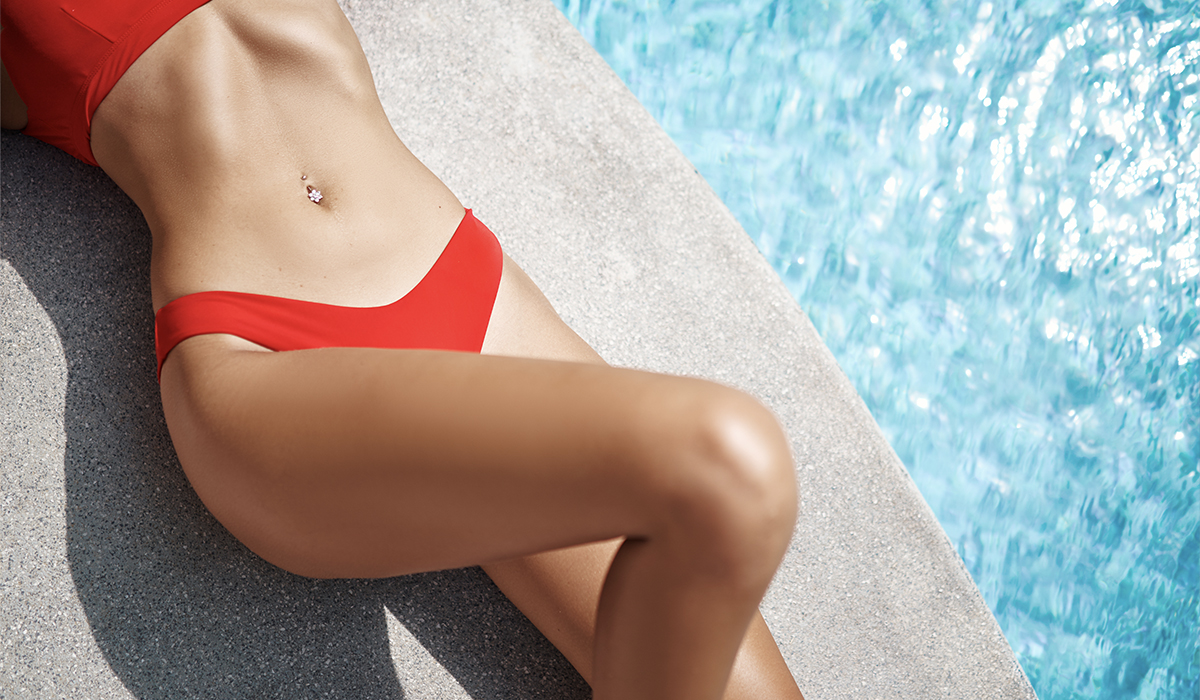 Woman with slim physique and stomach laying by pool