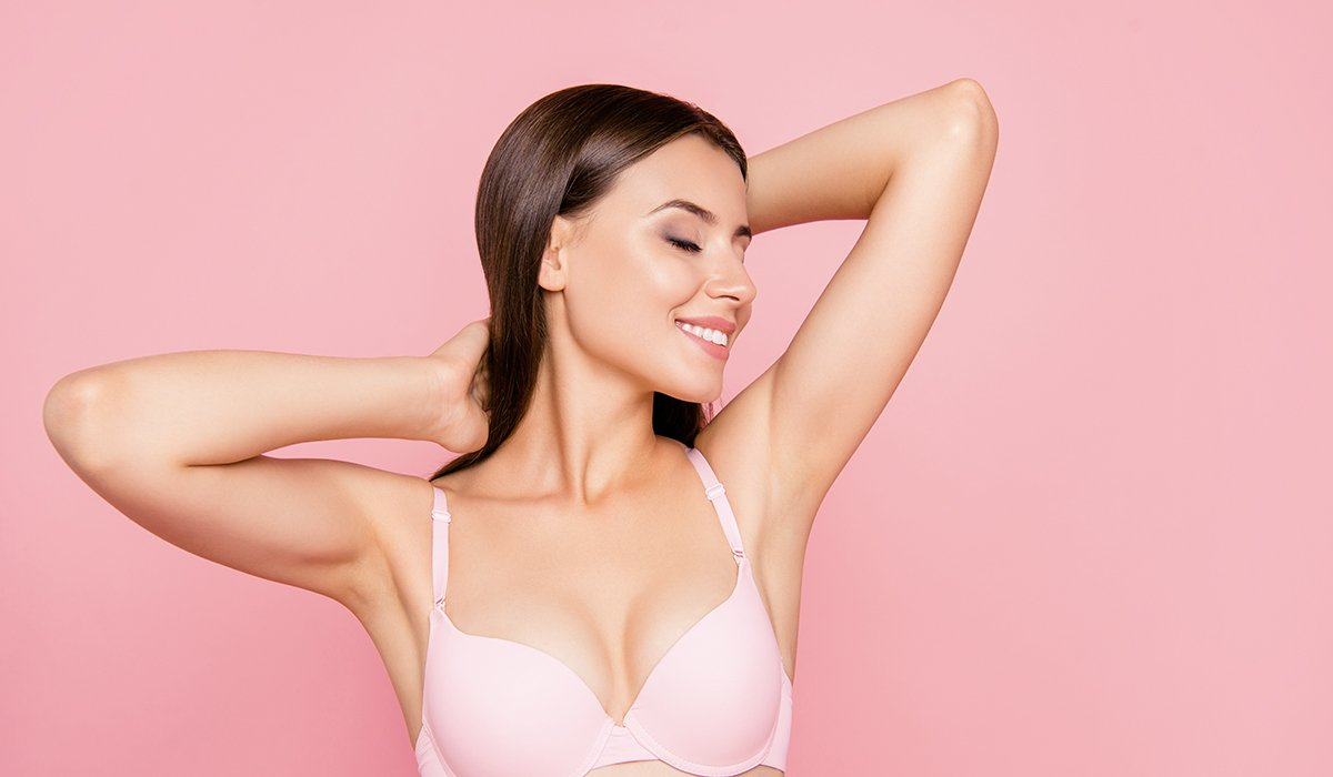 Young beautiful woman stretching and feeling hair on pink background