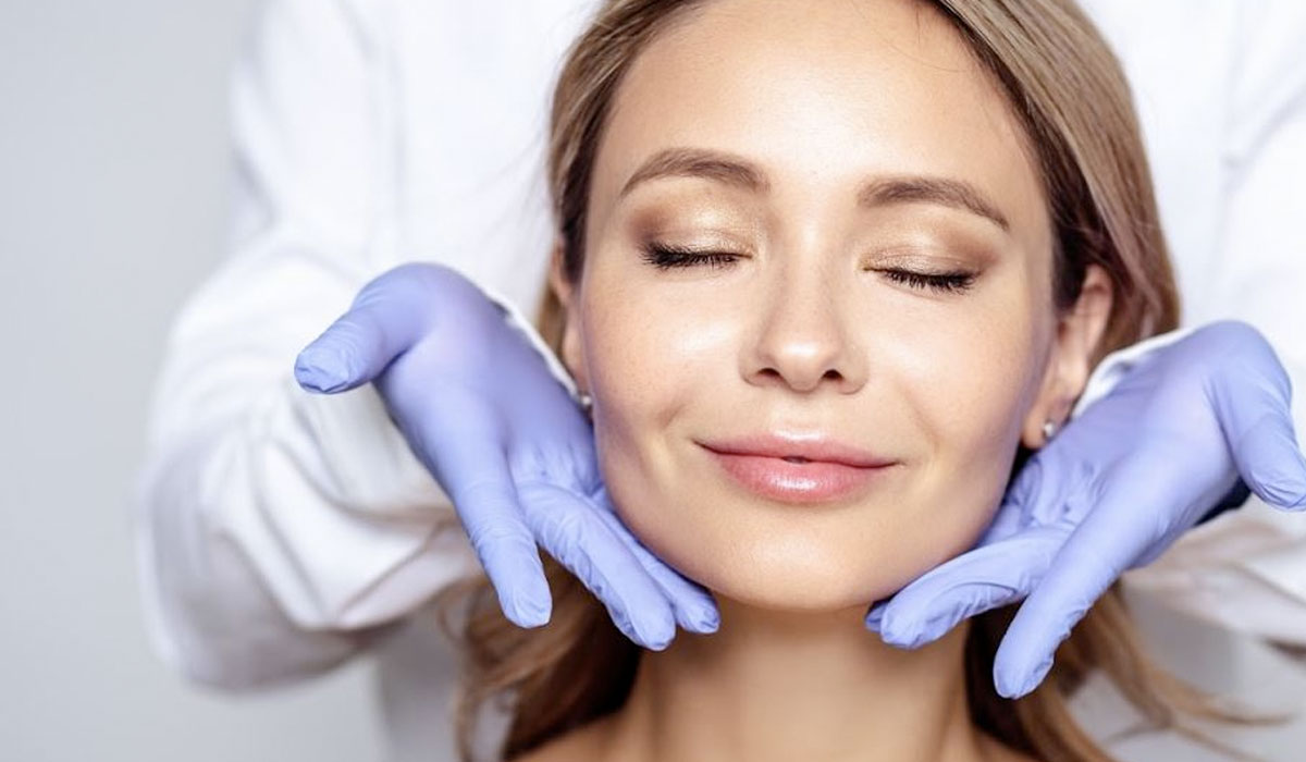 doctor presenting smiling womans face with hands on her chin
