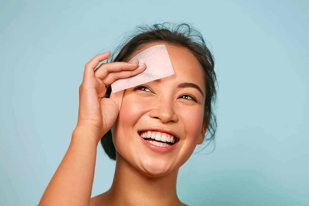 Asian american woman smiling and wiping face with cleaning pad
