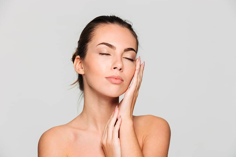Caucasian woman with pleasant look feeling smooth skin on face