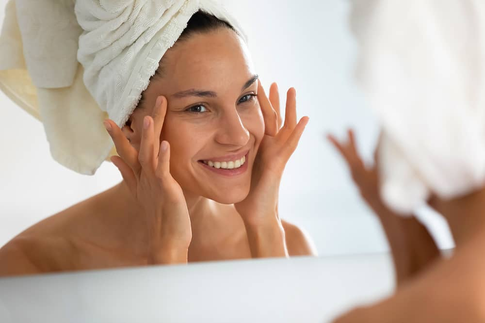 Woman with clear skin looking in the mirror with towel on head