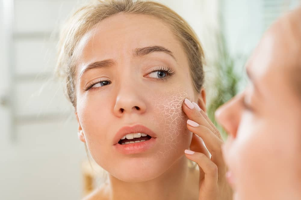 Young woman looking in mirror at dry skin on face