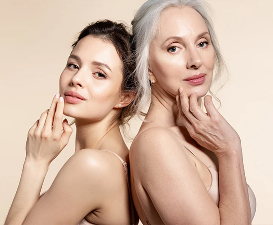 two women with smooth skin, one young, one old, standing back to back and looking at the camera