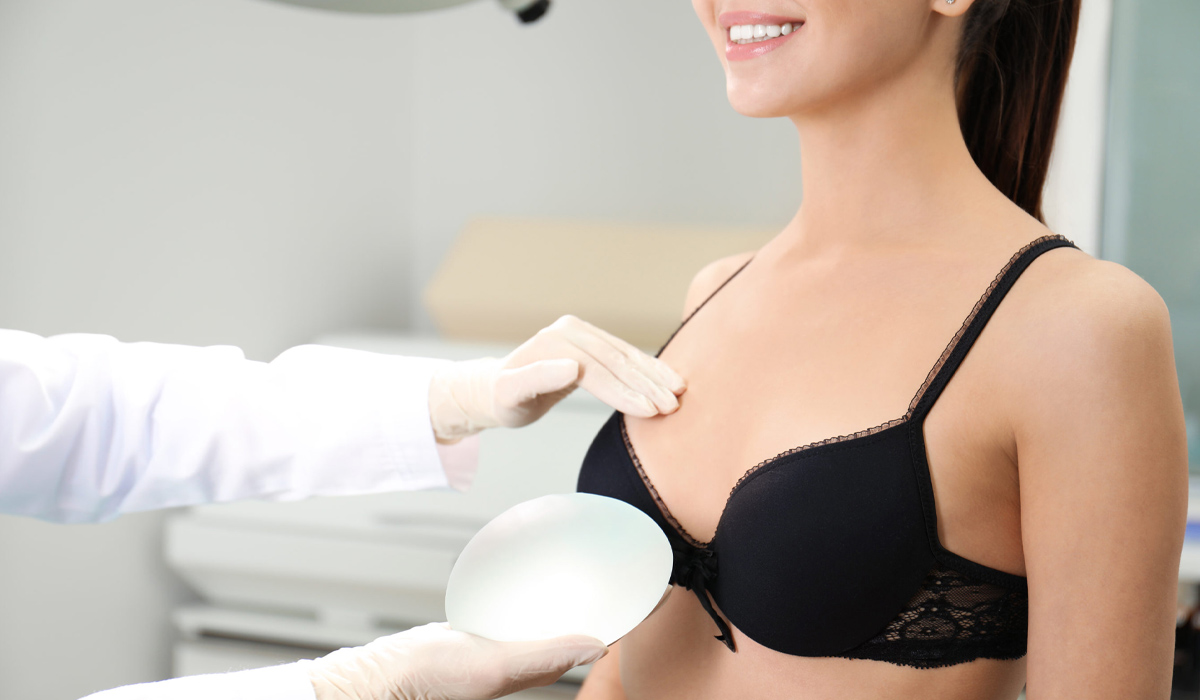 Doctor reviewing breast implant with female patient