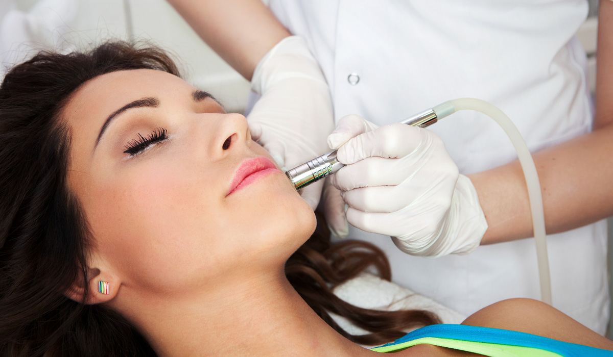 woman getting laser treatment procedure for her facial acne