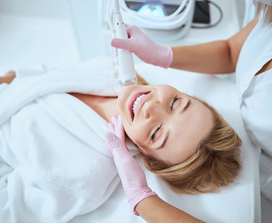 a woman in a robe smiling as she receives a microneedling procedure