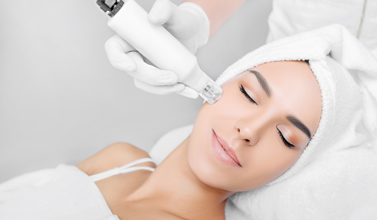 woman receiving no-needle high frequency mesotherapy at beauty salon.