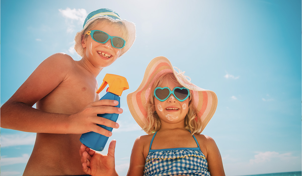 two children in sunglasses and bathing suits smiling at the camera with sunscreen on their faces