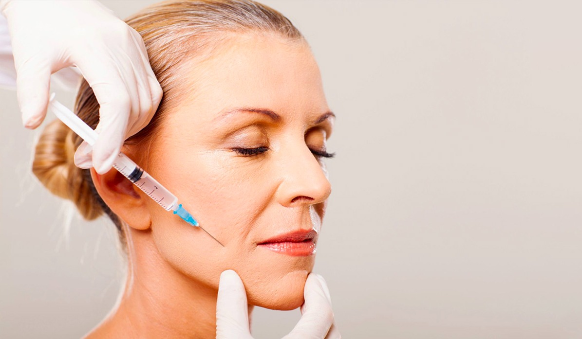 Older woman getting an injection to the side of her face to help reduce wrinkles